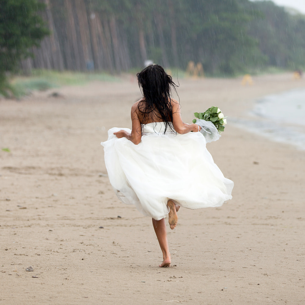 Bride running along the Beach