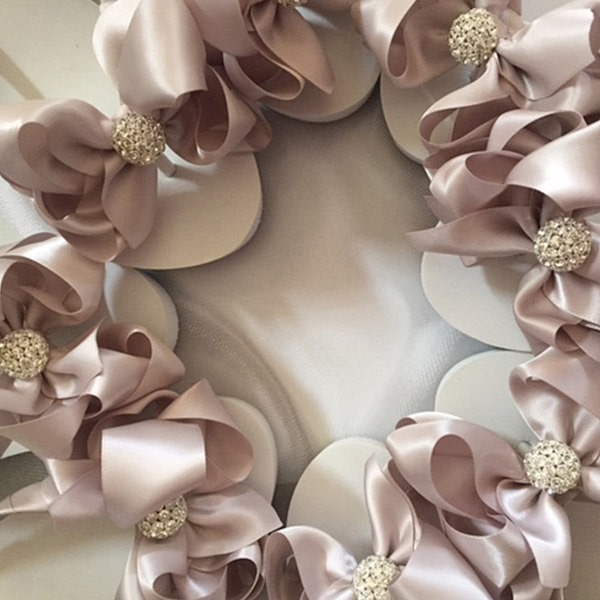Large latte coloured bows with rhinestone embellishments on high wedge heel flip flops