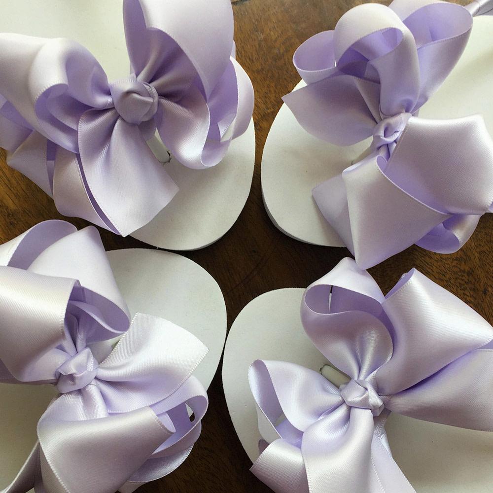 Large lavender coloured bows on high wedge heel flip flops