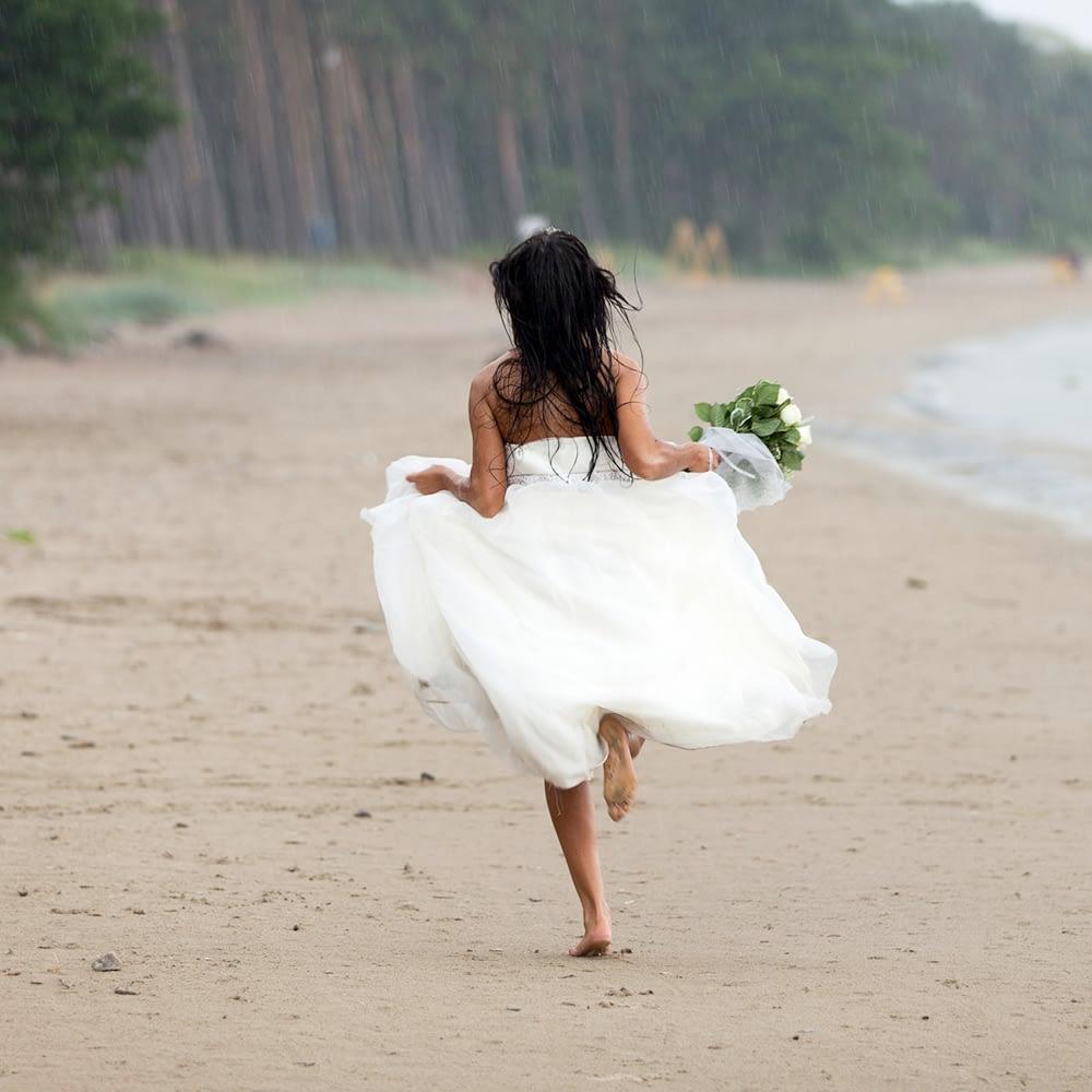 Bride running along the Beach