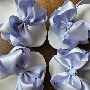 Large blue coloured bows on high wedge heel flip flops