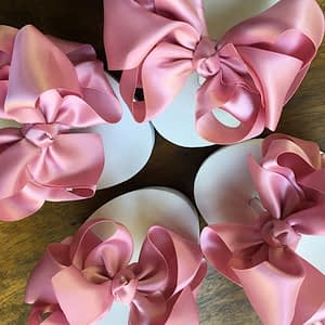 Large dusky pink coloured bows on high wedge heel flip flops