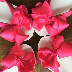 Large hot pink coloured bows on high wedge heel flip flops