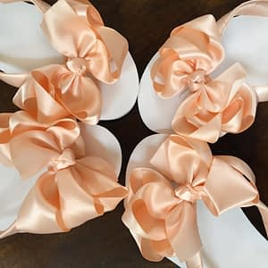 Large peach coloured bows on high wedge heel flip flops