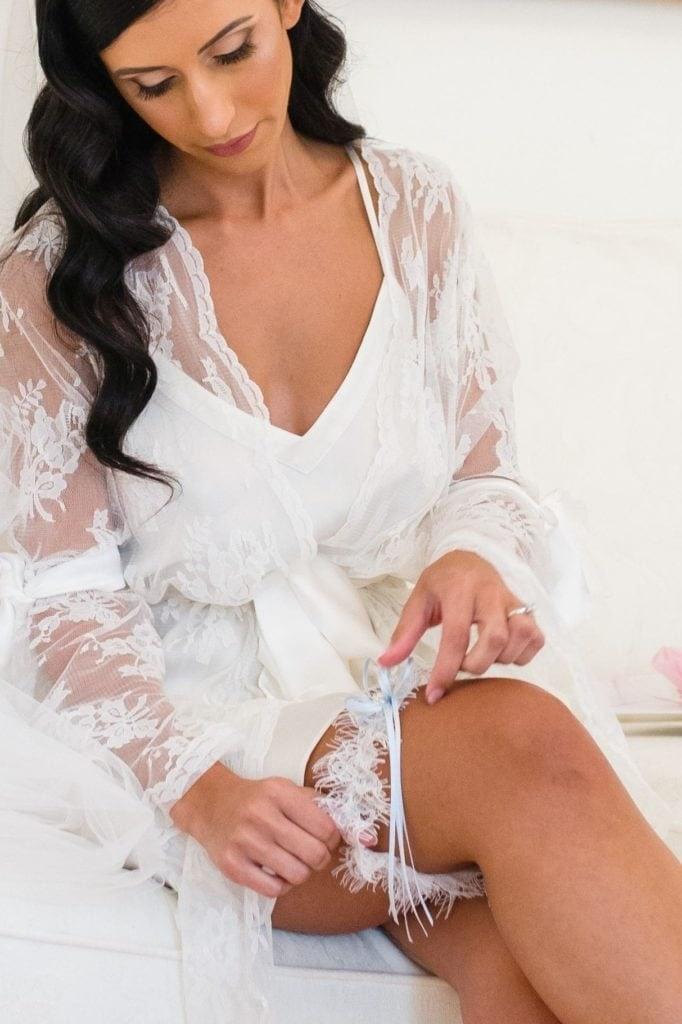 Bride in her robe slipping on her Wedding Garter