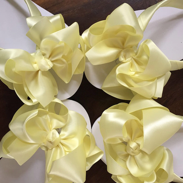 Large lemon coloured bows on high wedge heel flip flops