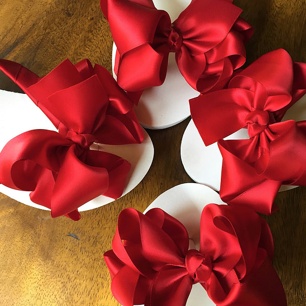 Large red coloured bows on high wedge heel flip flops
